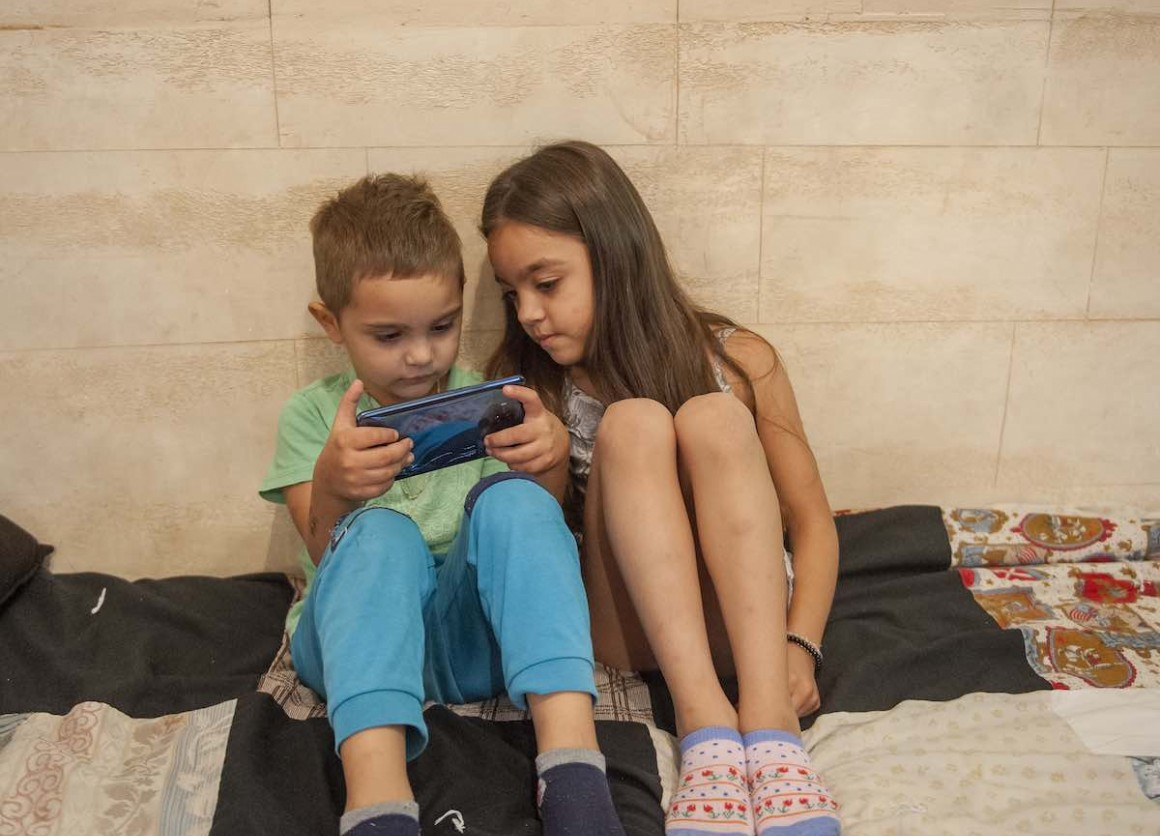 Andrej Madjupaj (4years) and Andjela Madjupaj (6 years) are playing a game on their phone, in their home in Roma settlement in Serbia.
