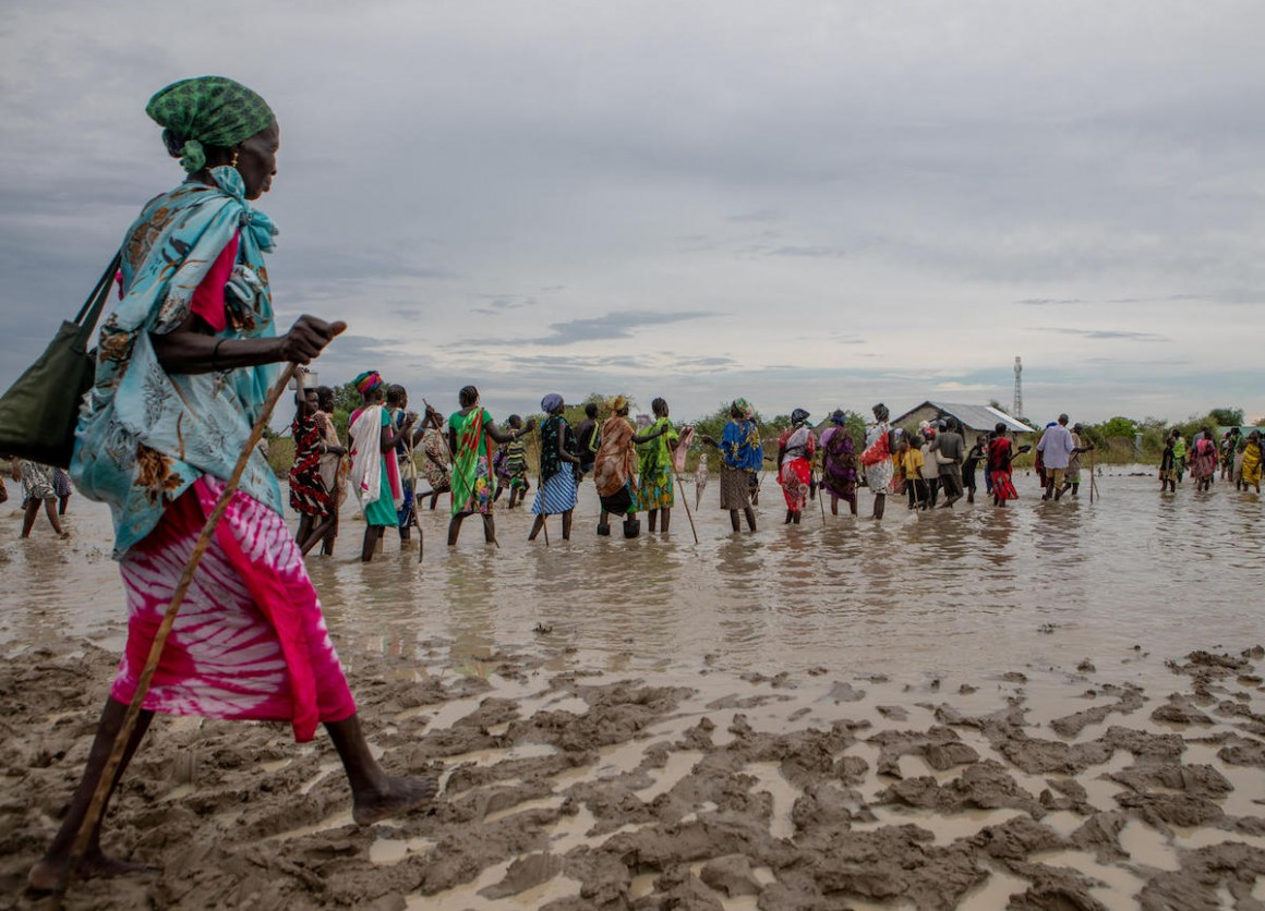Displaced families make their way back to temporary housing through flood water after a distribution point ran out of supplies in Pibor, Boma State, South Sudan on November 6, 2019.