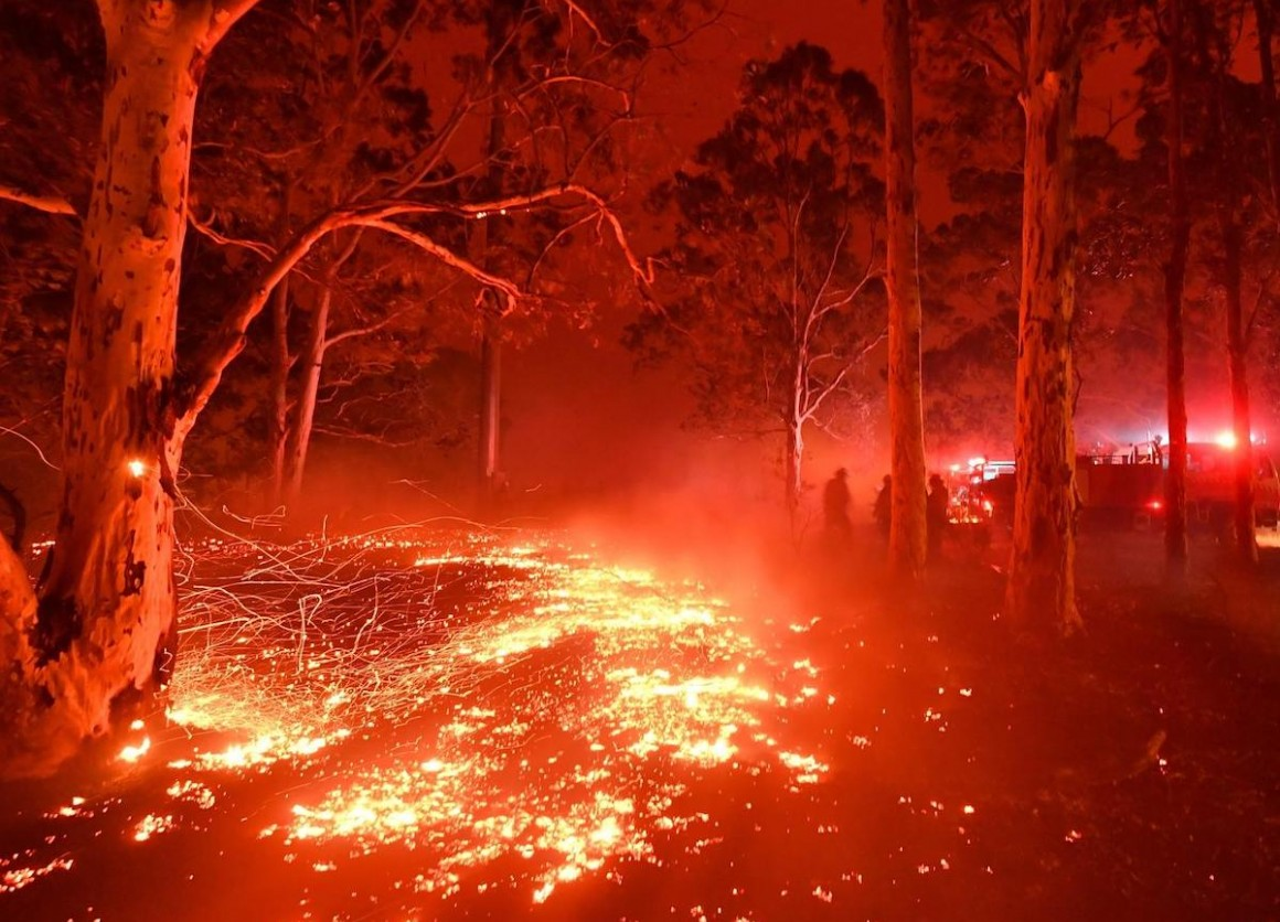 Burning embers cover the ground as firefighters battle against bushfires around the town of Nowra in the Australian state of New South Wales on December 31, 2019.