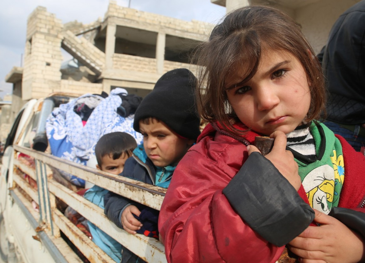Children ride on the back of a truck heading out of south rural Idlib, northwest Syria, where escalating hostilities have forced some 875,000 Syrians to flee since December 2019.