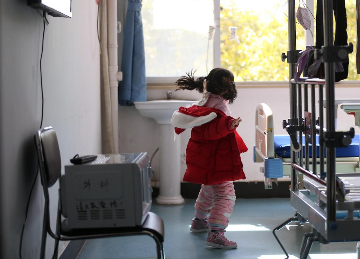 While her parents and grandmother are hospitalized with COVID-19, 5-year-old Yuanyuan jumps around in a ward in a hospital affiliated with the Wuhan University of Science and Technology in February 2020.