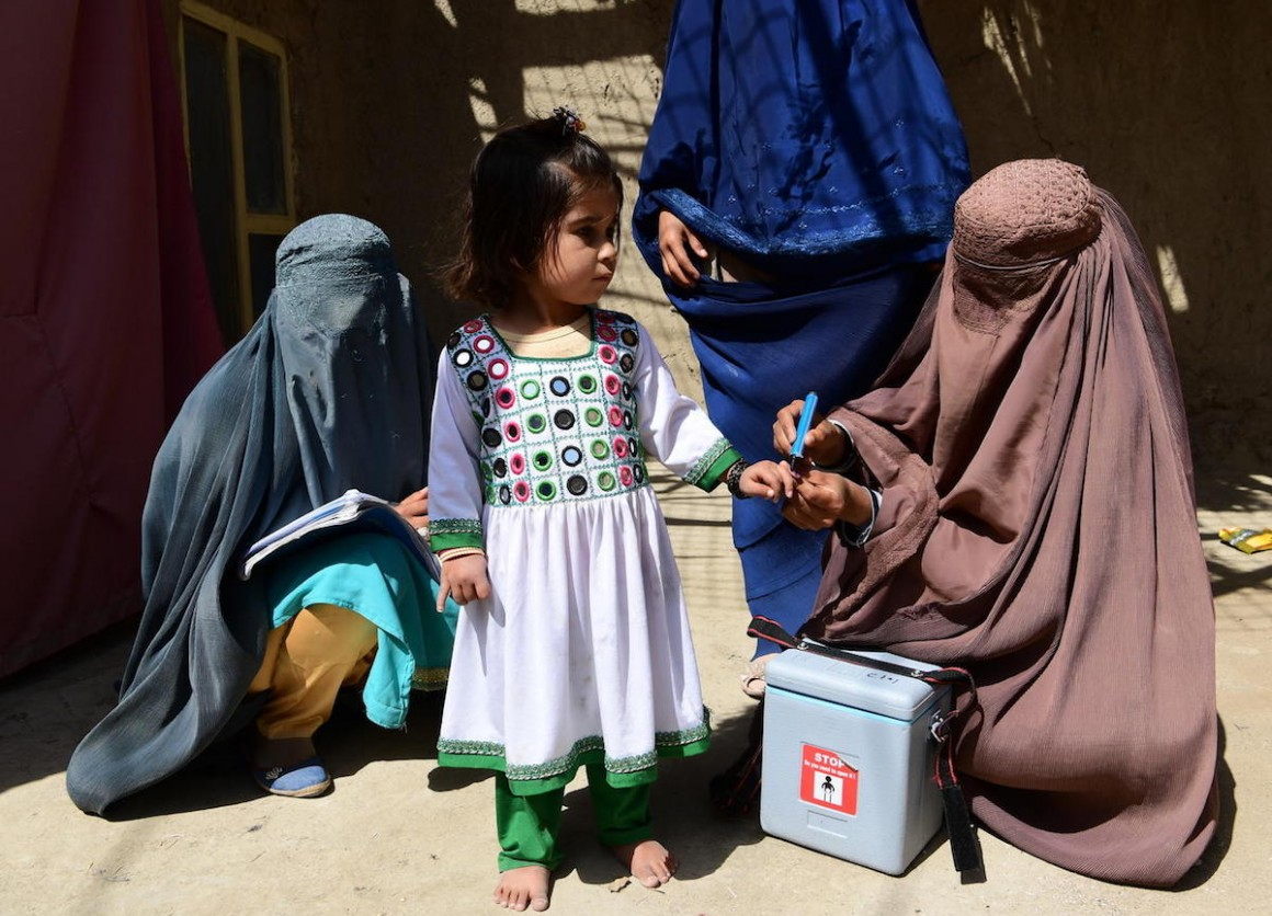 In Afghanistan's Kandahar Province on March 8, 2020, a UNICEF-supported polio vaccinator marks a girl's finger to indicate she has received the vaccine.