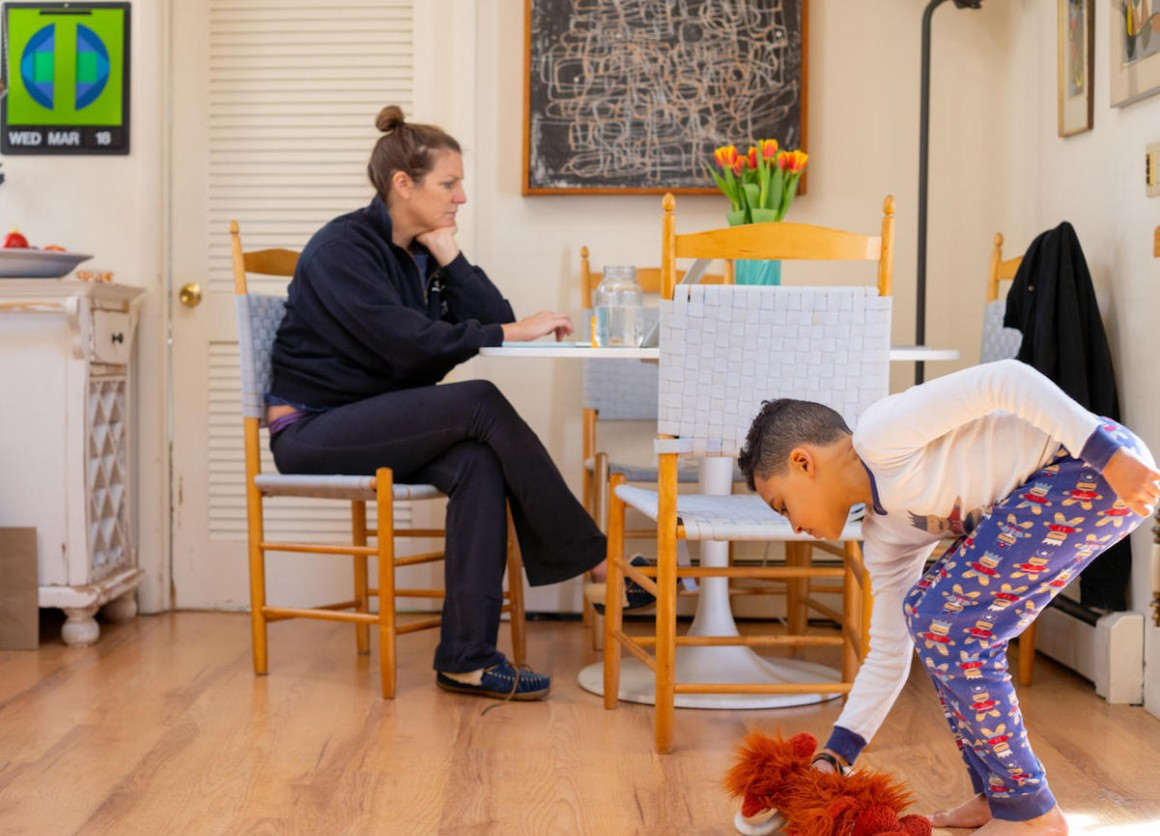 On the morning of 18 March 2020 in Connecticut, Luka, 8, plays with stuffed animals in between completing school exercises on his third day of distance learning from home, while his mother, Sophia, works on her computer.