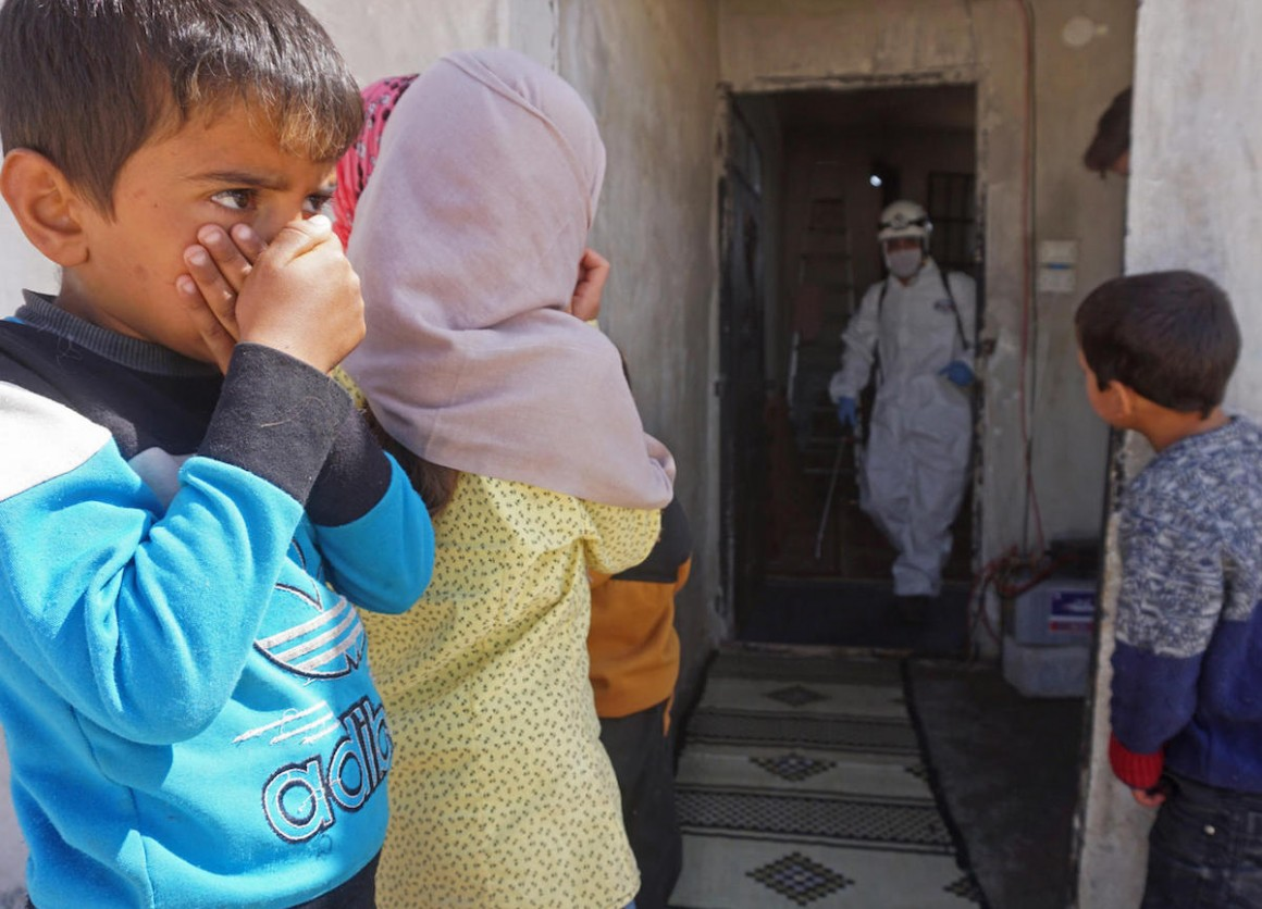 Syrian children watch a member of the Syrian Civil Defence, known as the White Helmets, disinfecting a former school building currently inhabited by displaced families in the town of Binnish in northwestern Idlib Governorate, Syria, on March 26, 2020.