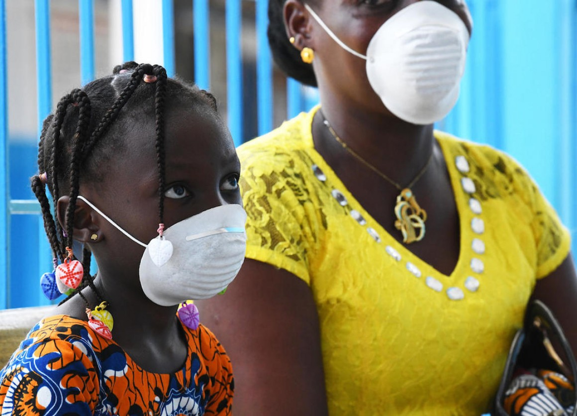 A mother and daughter wear masks during a visit to the UNICEF-supported health center outside Abidjan, in the south of Côte d'Ivoire, to protect them from COVID-19.