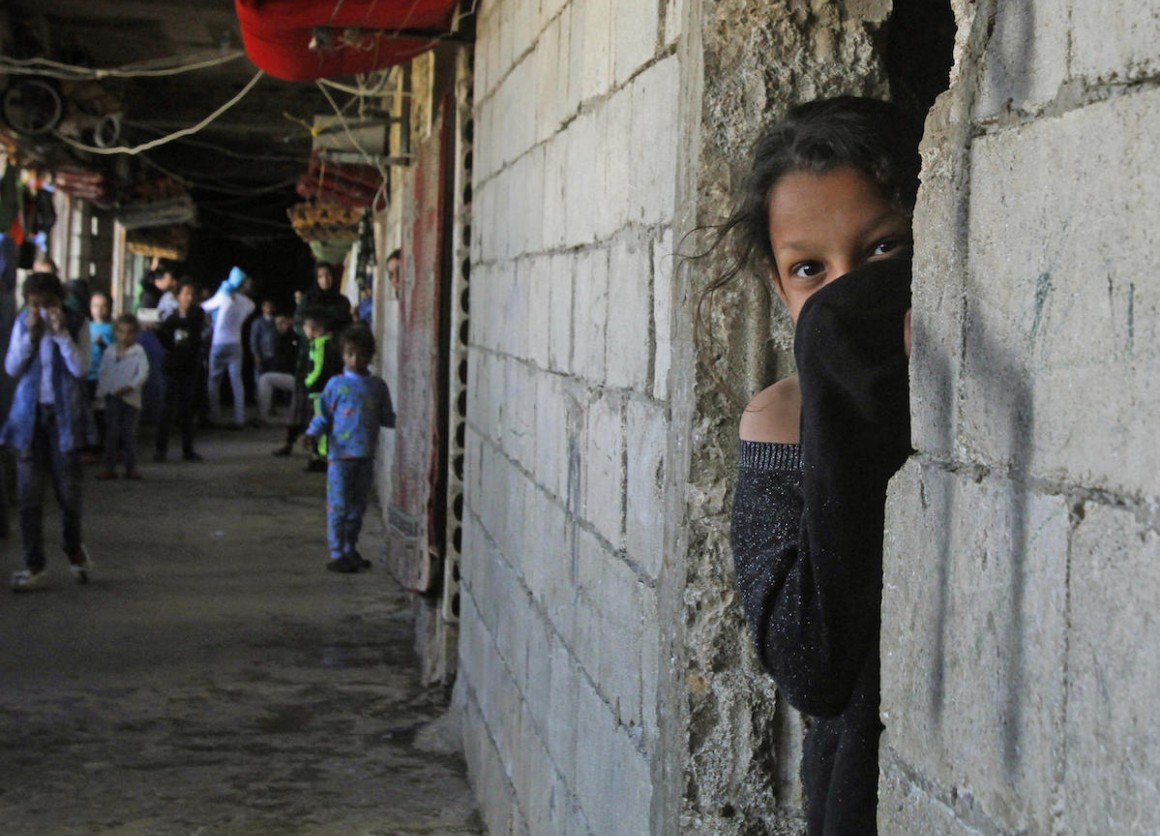 On March 17, 2020, a Syrian refugee, her face covered to protect against COVID-19, looks out from a doorway in an unfinished building where she has been living in the city of Sidon in southern Lebanon.