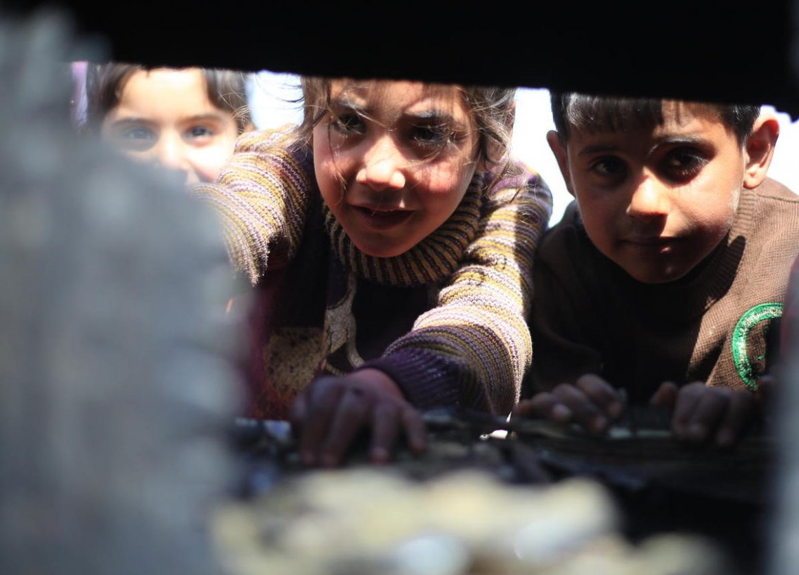 On April 5, 2020, at a tent camp in Idlib in northwestern Syria, children sift through the wreckage left when their family's tent caught fire from a gas stove.