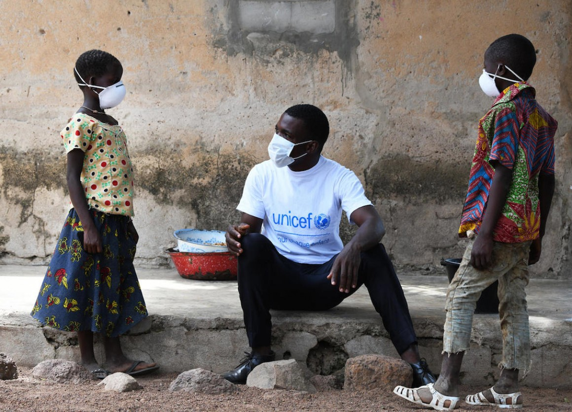In the village of Morovine, in the North of Côte d'Ivoire, a UNICEF Staff member counsels children on the importance of wearing masks or face coverings to protect themselves against the coronavirus.