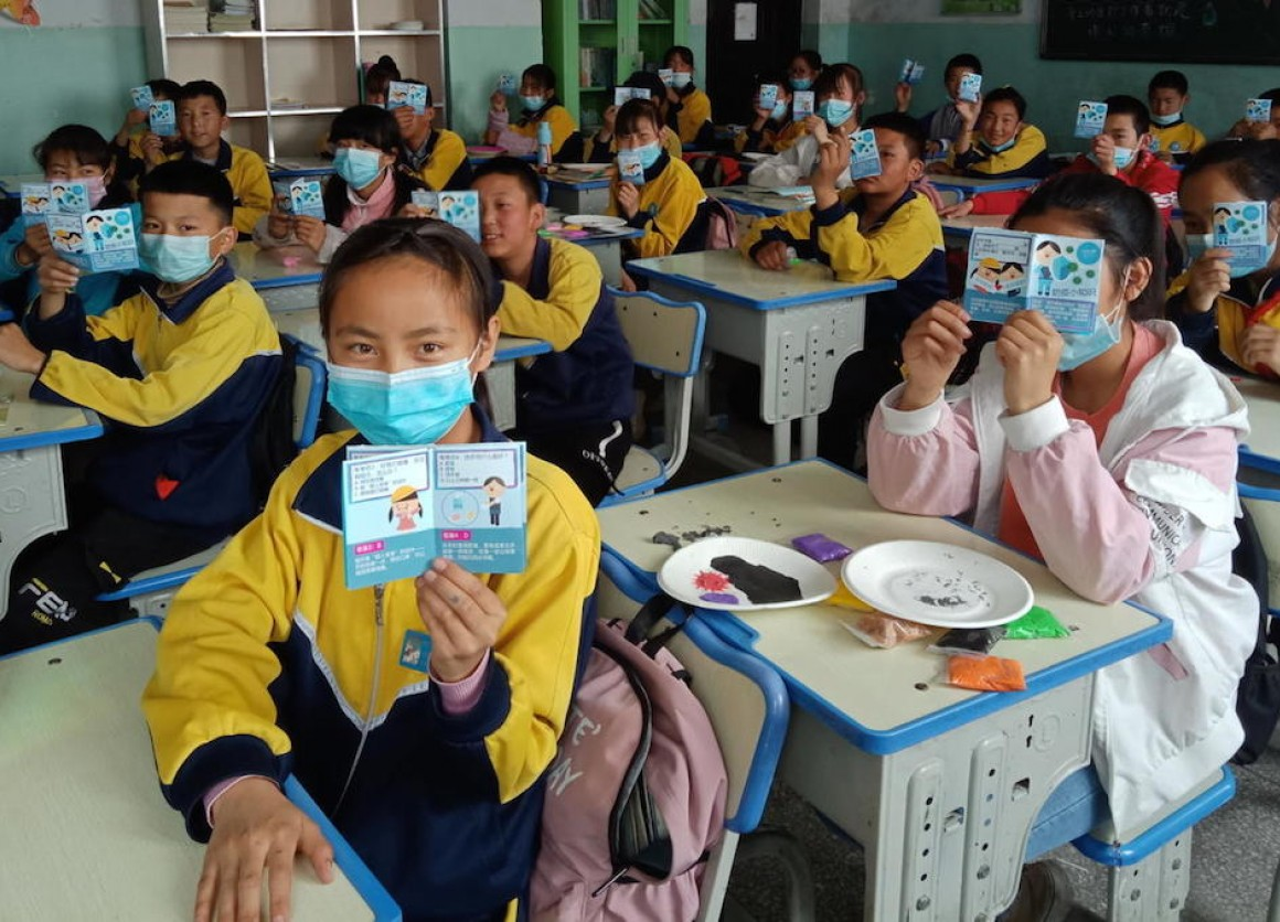 Students at a school in Datong County, Qinghai Province, China, hold up health education leaflets developed by UNICEF as part of the response to COVID-19.