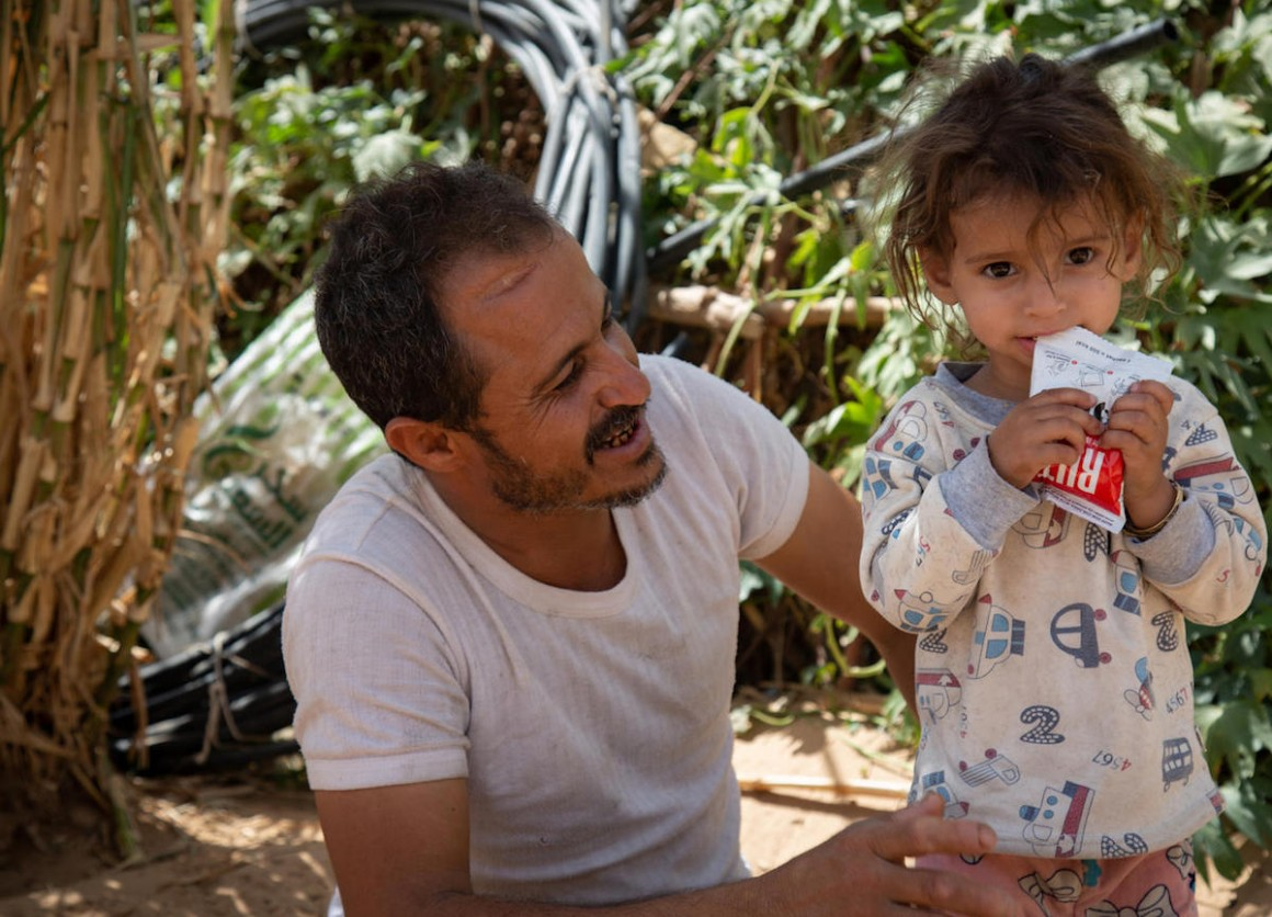 Moharram Al-Oshari smiles at his 2-year-old daughter, Bulqis, who is being treated for severe malnutrition by UNICEF-supported health workers in Yemen's Marib governate.