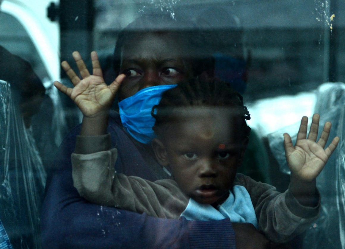 A migrant child and her mother on a bus headed to Toncontin international airport in Honduras, where they will be tested for COVID-19 and quarantined for two weeks.