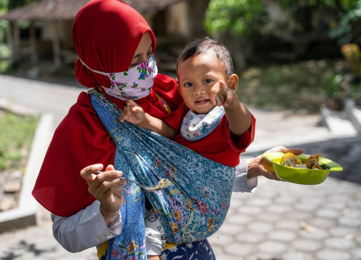 Dini feeds her year-old son Abdullah at their home in Paseban village, Central Java province, Indonesia.