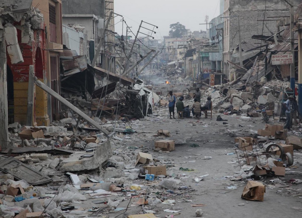 On January 19, 2010, men gather at a table and chairs set up in the middle of a street devastated by the earthquake, in Port-au-Prince, Haiti's capital.