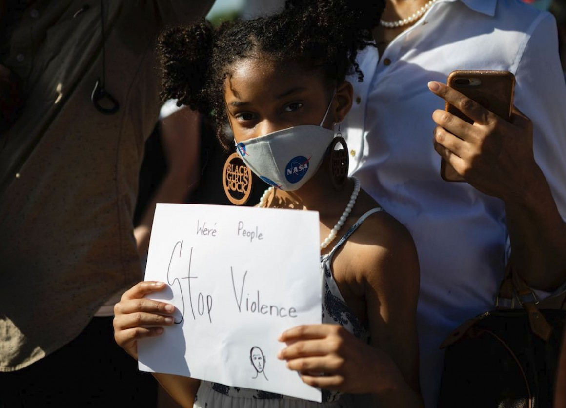 A young black girl holds a simple but powerful poster as she protests against racialized violence