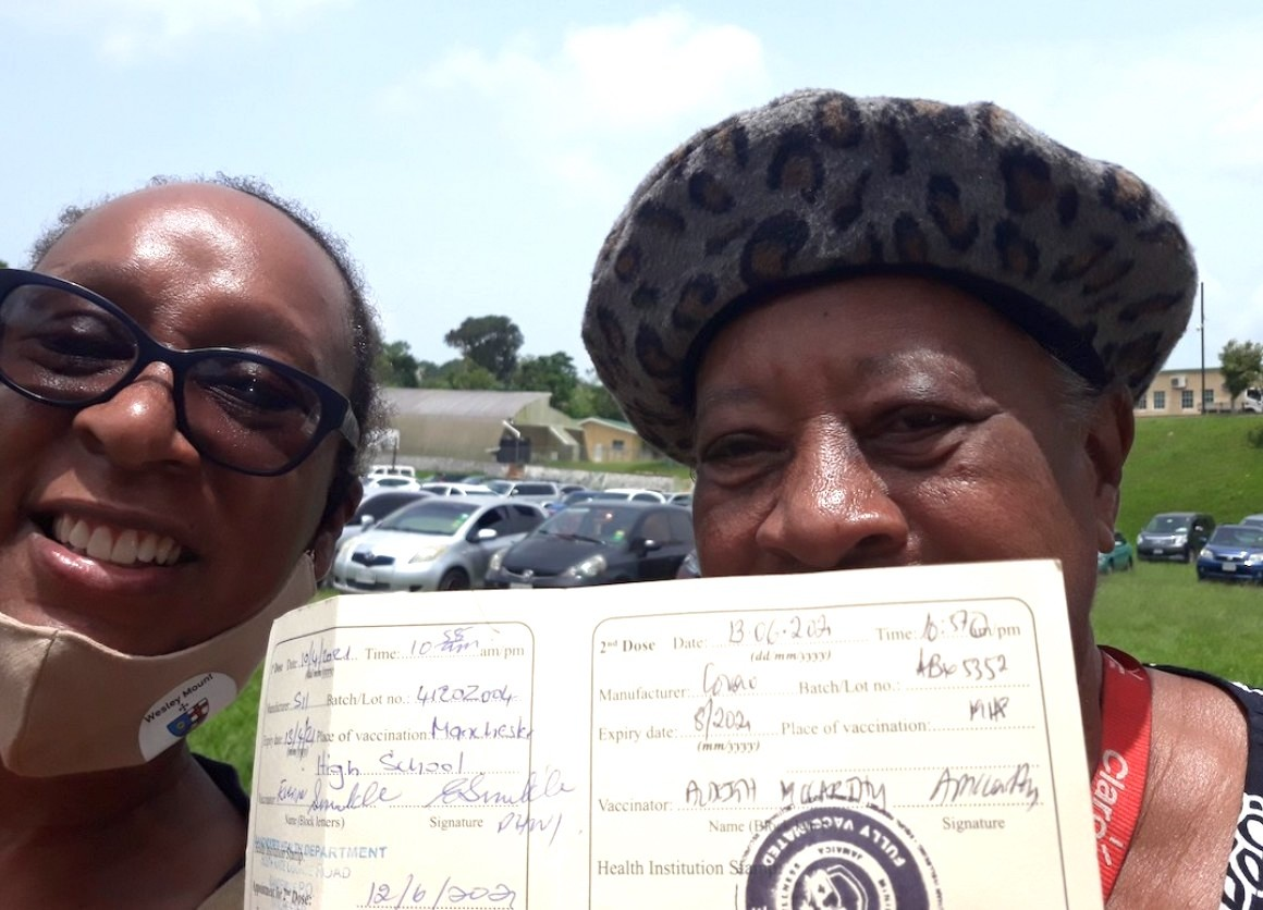 Gail Hoad of UNICEF Jamaica, left, with her mum holding her vaccination card on COVID-19 vaccination day in Manchester parish, Jamaica, June 13, 2021.