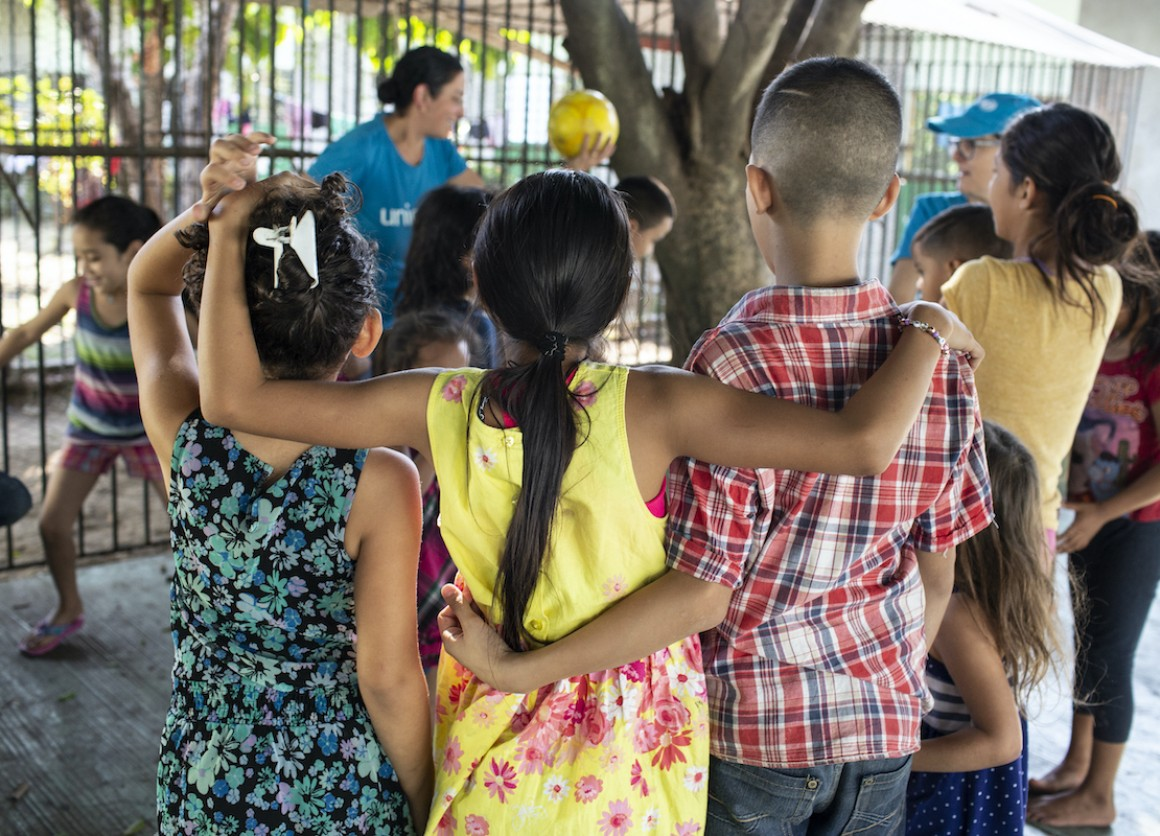 A UNICEF-supported volunteer plays with children at the St. Augustine hotel for refugees and asylum seekers in Tapachula, Mexico.