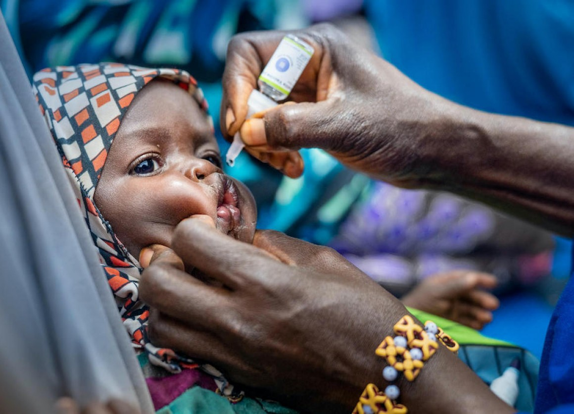 A volunteer community mobilizer administers the oral polio vaccine to a child in Fanisau Ugongo Village, Kano State, Nigeria.