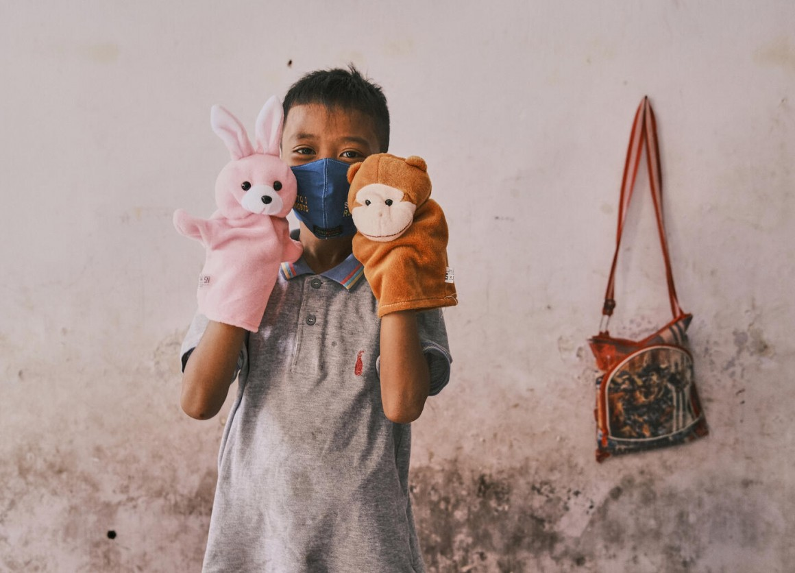Dwi Rizky Saputra plays with toys from a recreational kit he received for children affected by COVID-19 at his home in Jombang, Indonesia, on 22 October 2020.