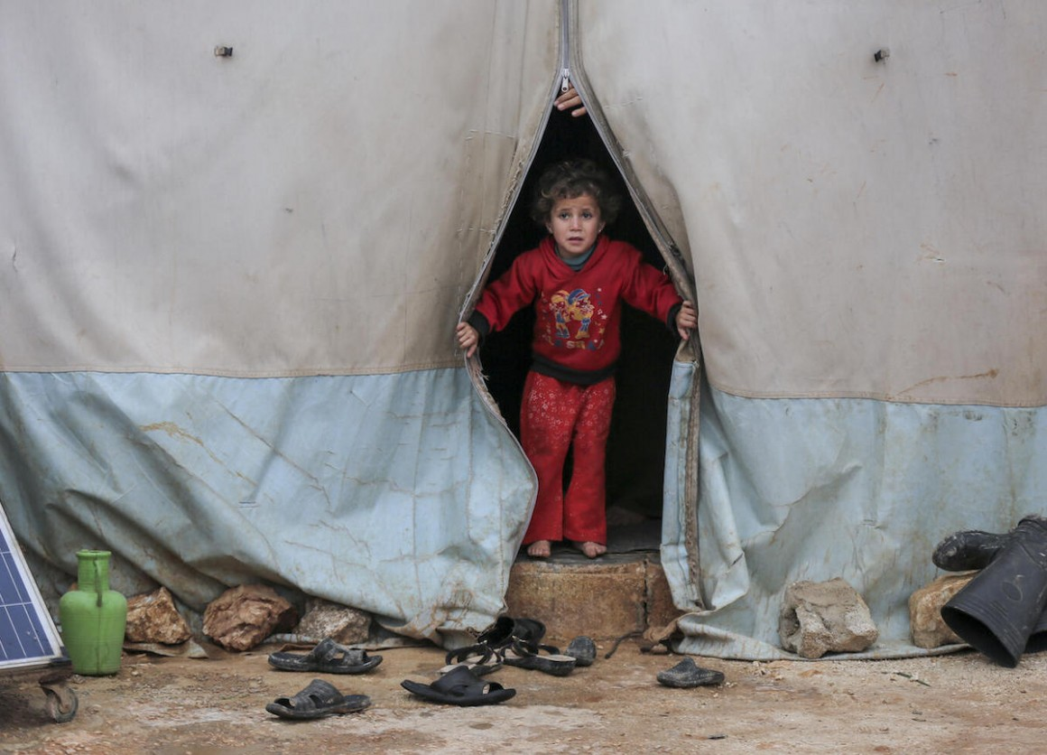 On 19 January 2021, a child looks out a tent in Kafr Losin Camp in northwest Syrian Arab Republic. UNICEF is working with partners to provide displaced children in Syria with the supplies and services they need to survive and thrive.