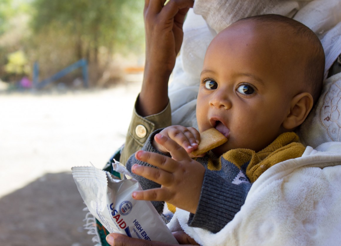 An infant eats a nutritional biscuit supplied by UNICEF as part of ongoing relief efforts for children and families displaced by violence in Ethiopia's Tigray region.