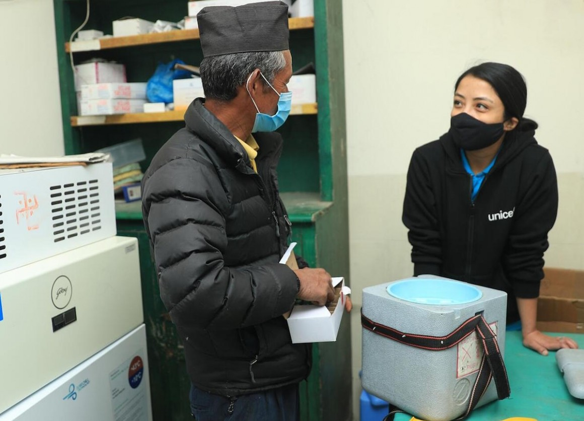Mitthi Jirel (left), staff at the district hospital in Jiri in Dolakha District in northeastern Nepal, with UNICEF staff Preena Shrestha (right) in the hospital's vaccine storage room on February 26, 2021.