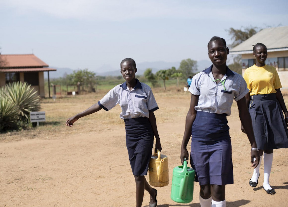 From left: 17-year-olds Margaret and Elizabeth, and Nite, 19, carry water from the newly rehabilitated borehole at Ilumum Primary School in Torit, South Sudan.