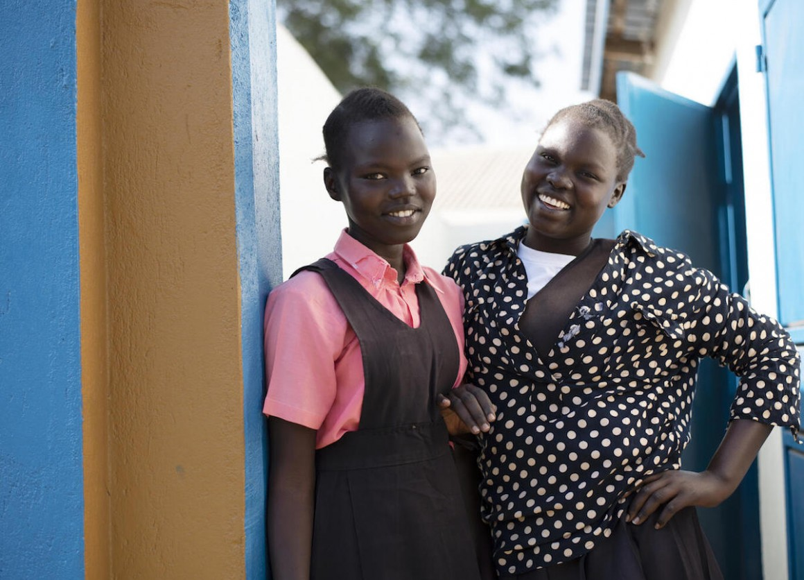 On February 3, 2021, Keziah, 14, (left) and Elizah, 16, stand in front of the newly rehabilitated latrine at AIC Nursery and primary school in Torit, South Sudan..
