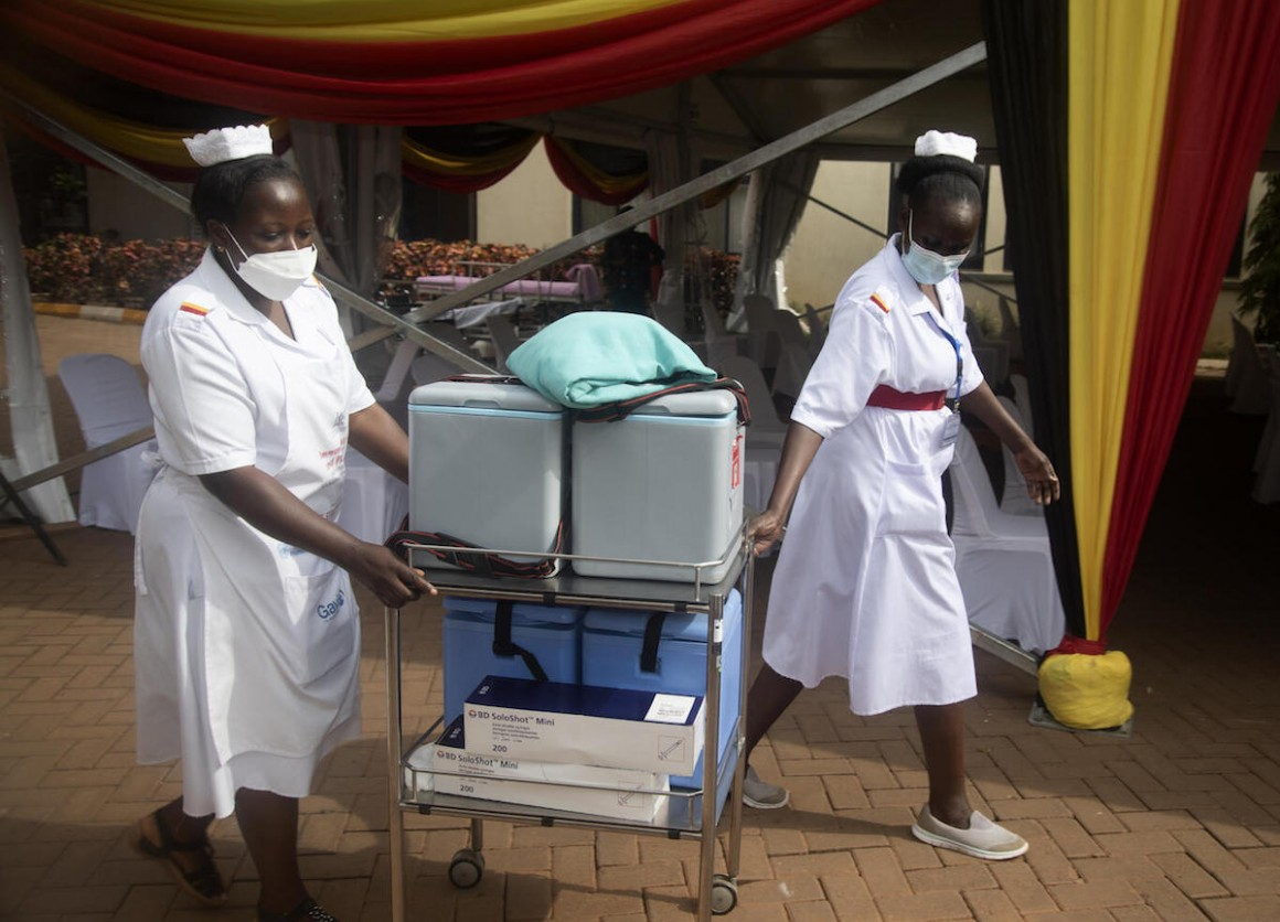 Health workers move vaccine cooler boxes to vaccination points at the official launch of COVID-19 vaccination efforts in Uganda at Mulago National Referral Hospital on March 10, 2021.