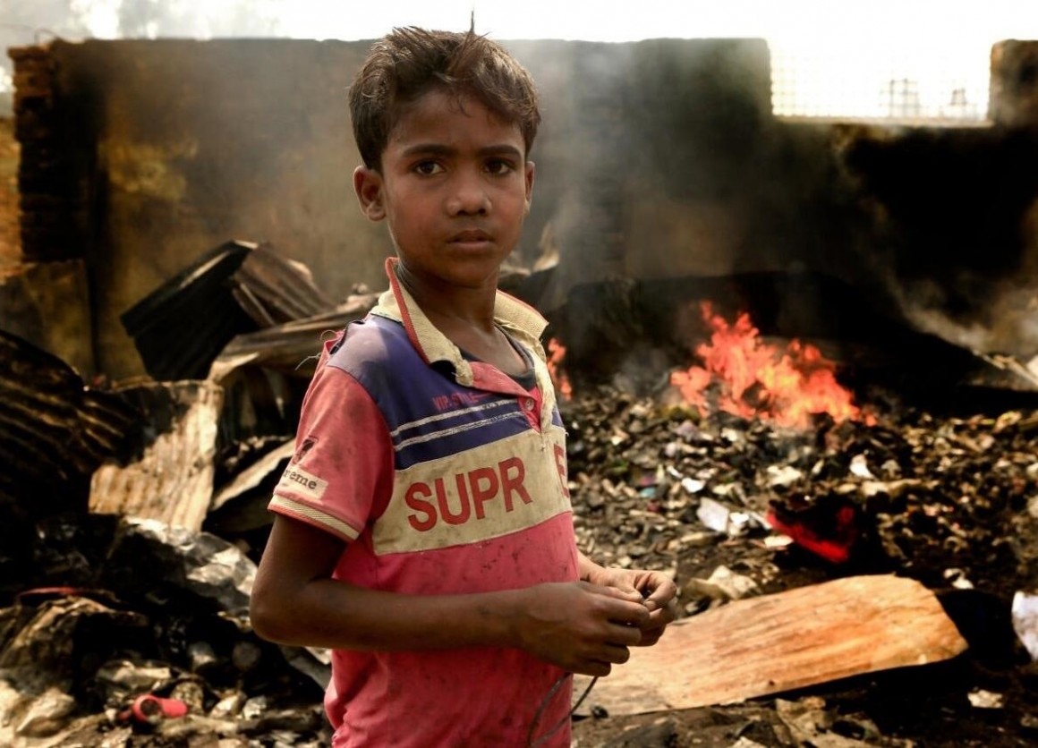 On March 23, 2021, 10-year-old Rezwan stands in the fire-damaged wreckage of the Balukhali area of the Rohingya refugee camps in Cox's Bazar, Bangladesh.