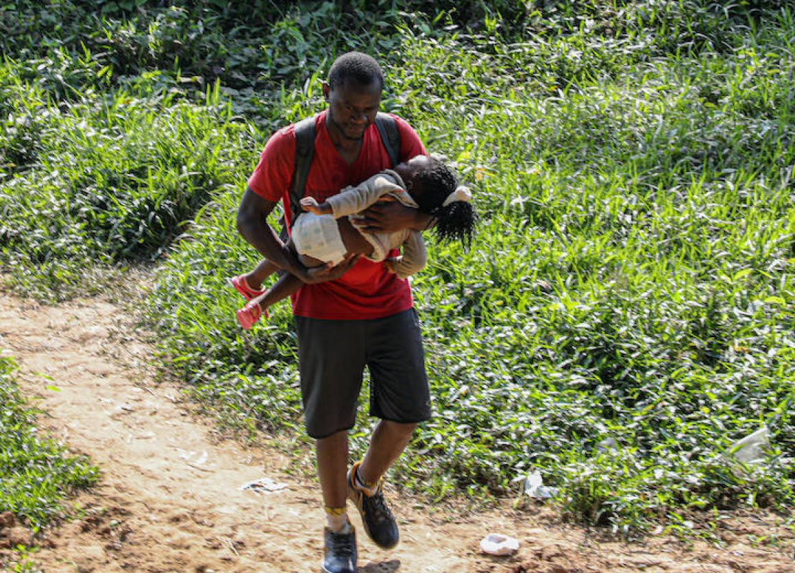 A father and child arrive in Bajo Chiquito, Panama, after crossing the Darien Gap, one of the most dangerous migration routes in the world.
