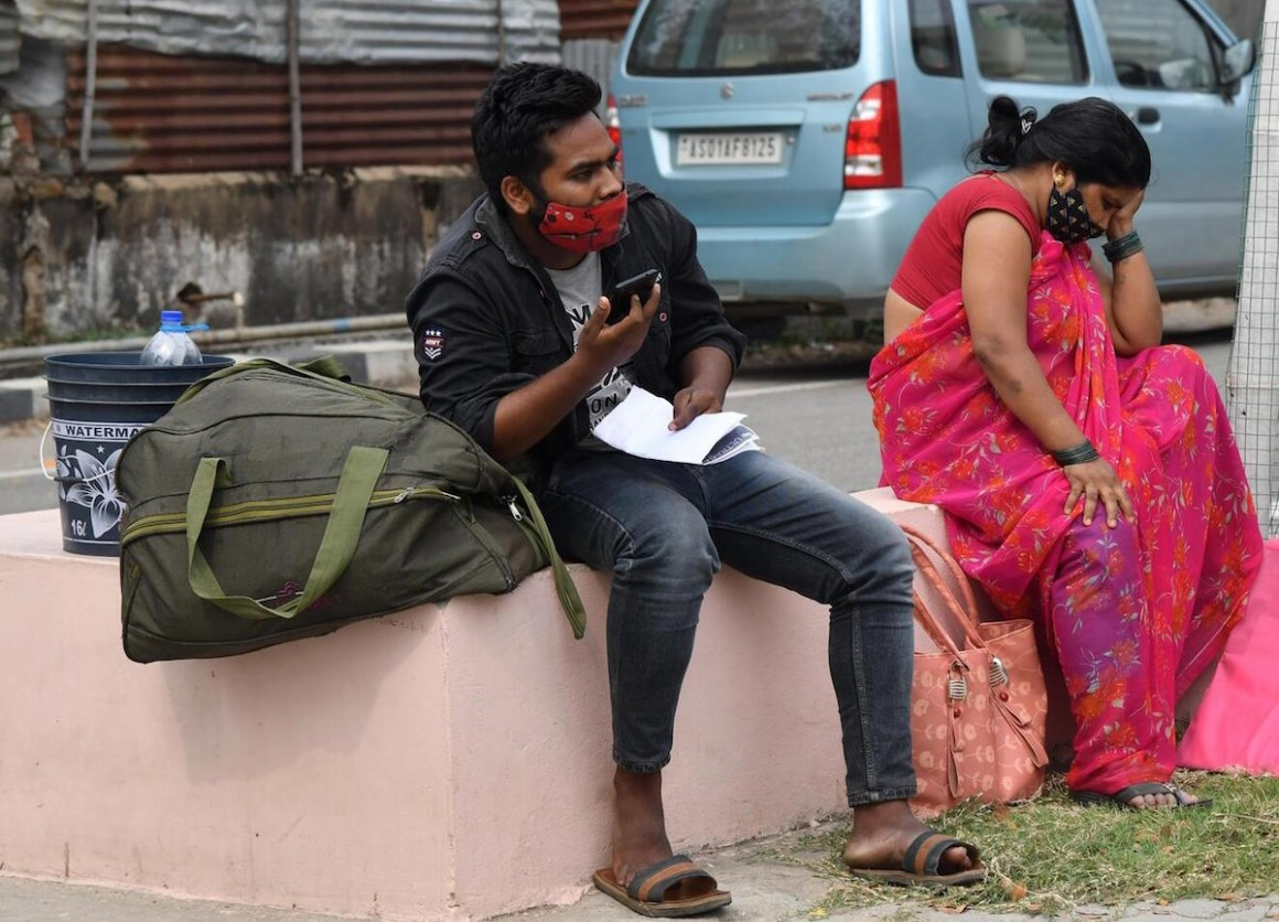 COVID-19 patients sit outside the Gauhati Medical College COVID Care Hospital in Kalapahar, Guwahati, India, where all beds are full on April 30, 2021.