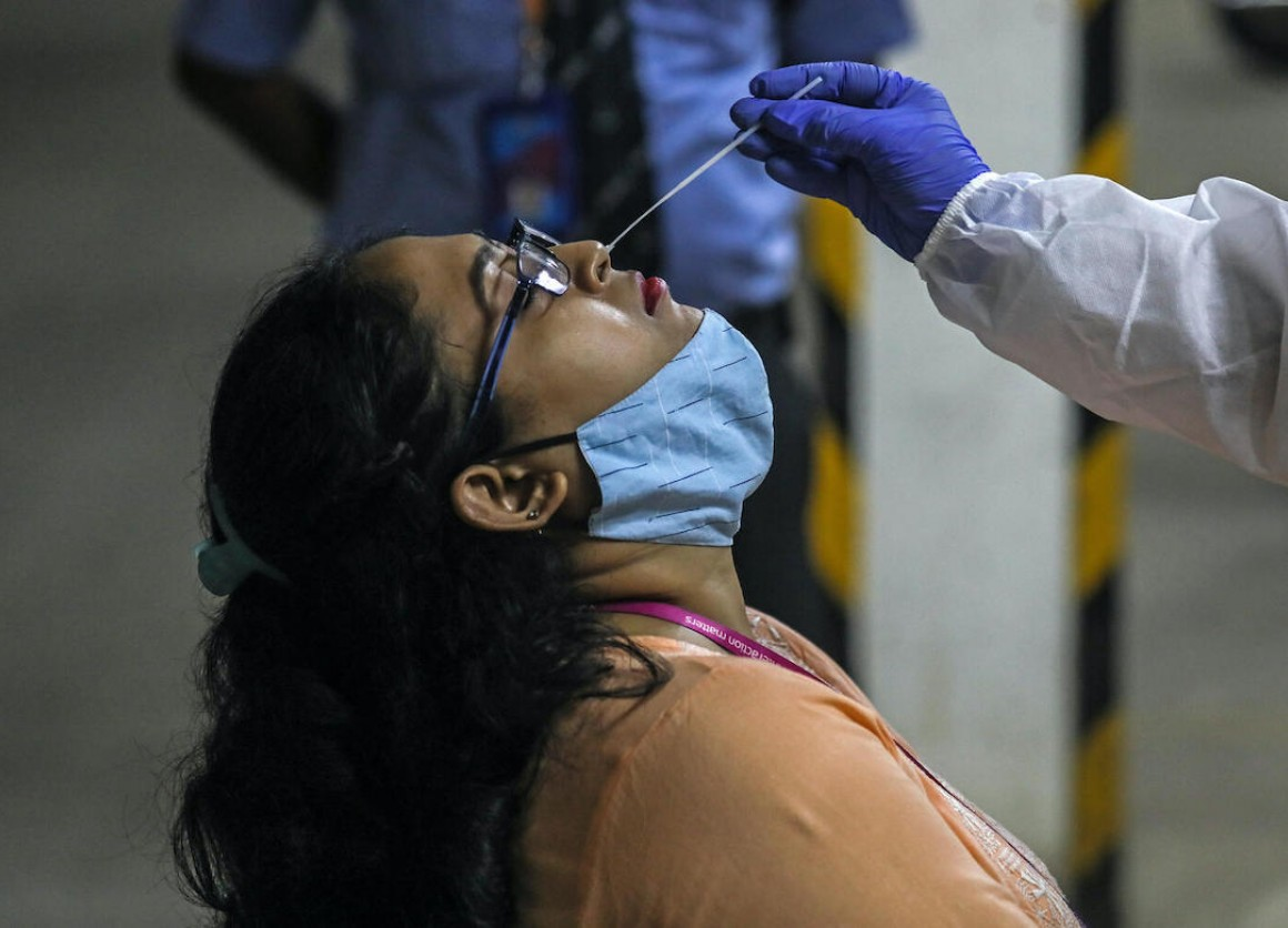 A health worker takes a nasal swab sample to test for COVID-19 at a facility in the Malad area of Mumbai, India, on April 30, 2021.