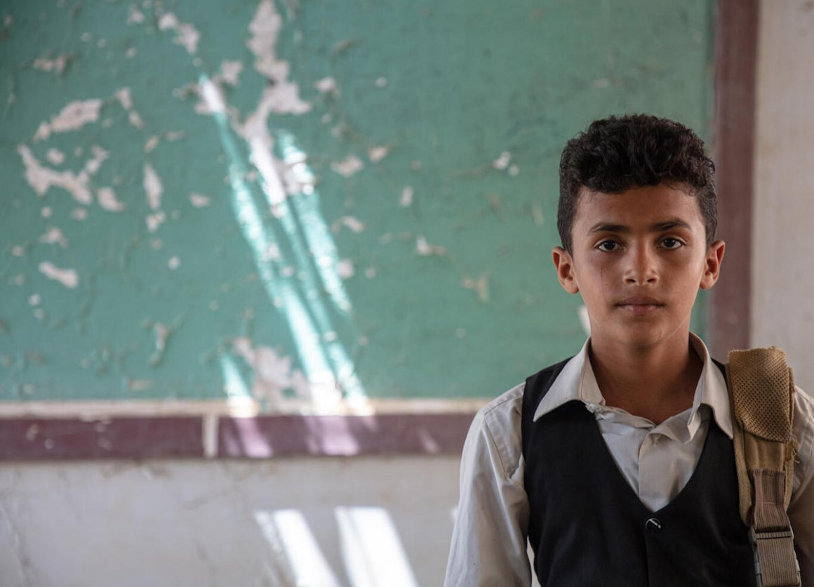 Twelve-year-old Ahmed standing in his classroom in Al-Hamzi school, which was damaged by the conflict in 2015, in Yemen's Hajjah governorate, March 2021.