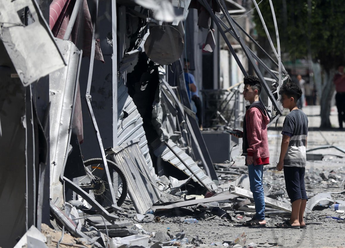 On May 17, 2021, Palestinian children walk in front of a house that was targeted by the Israeli bombardment in Gaza City.