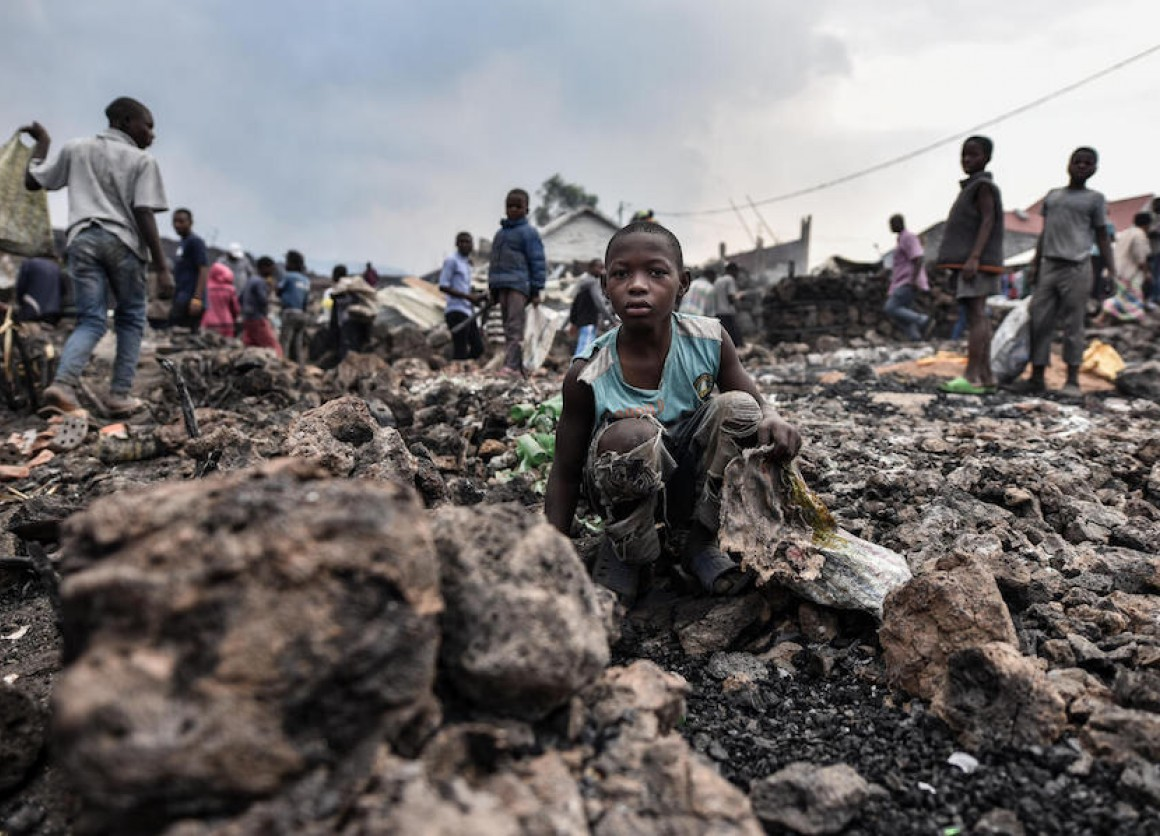 Children stand amidst lava from the volcanic eruption of Mount Nyiragongo, which occurred late on May 22, 2021 in eastern Democratic Republic of the Congo.