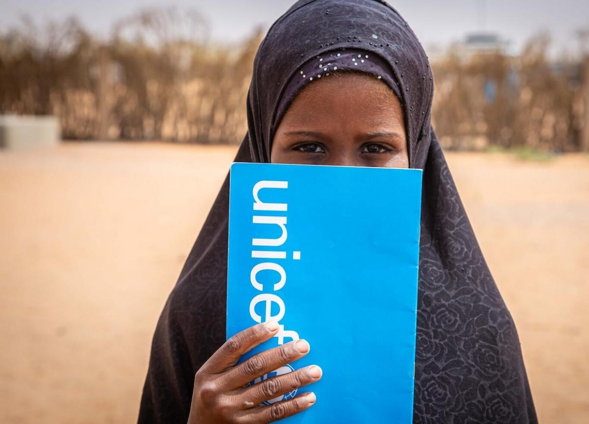 A student peeks out from behind her UNICEF notebook in Mbera refugee camp in southeastern Mauritania in 2021.