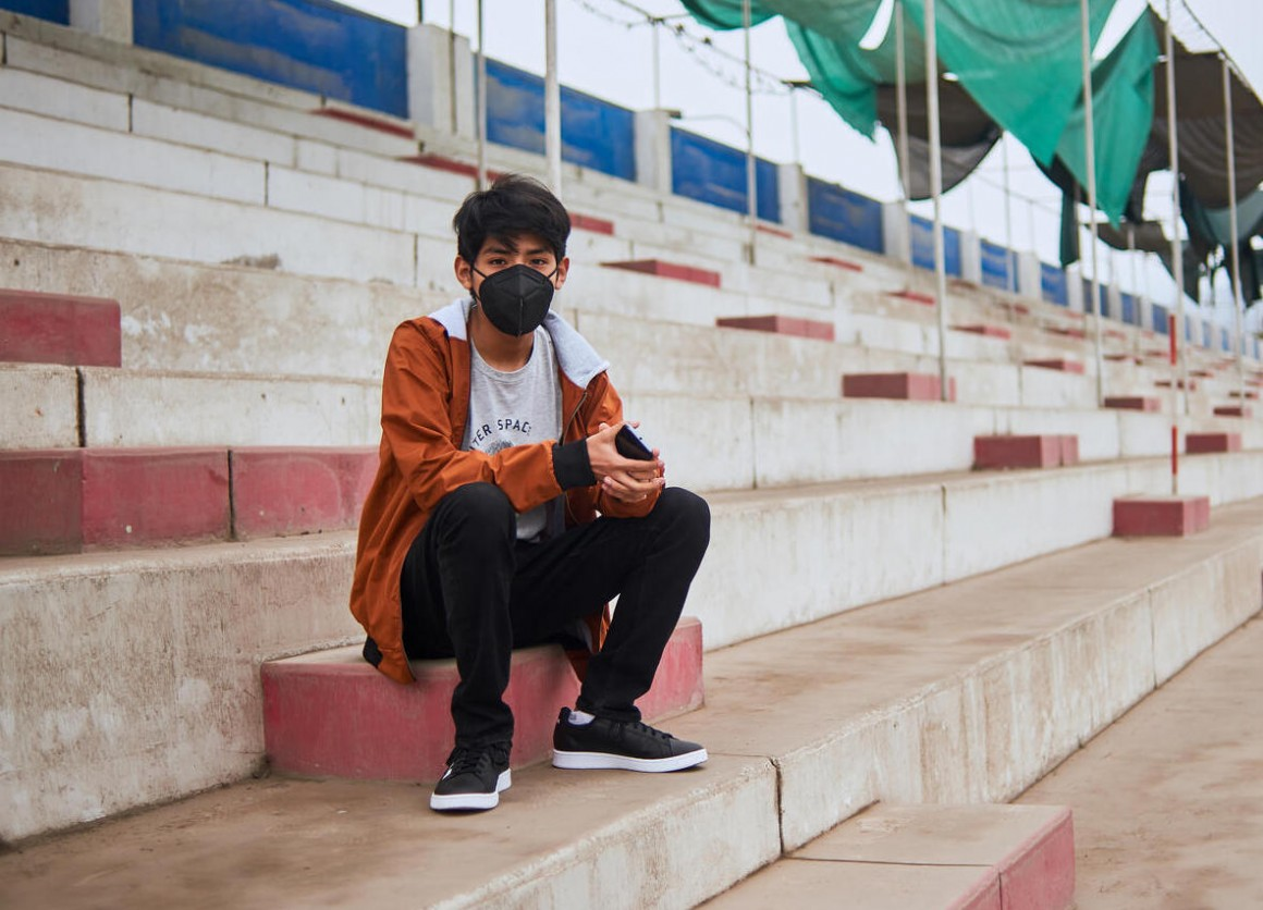 Andre, 14, sits in the stands of a repurposed sports stadium in Carabayllo, a district in the north of Lima, Peru, while he waits for his scheduled appointment at the UNICEF-supported Community Mental Health Center that occupies one of the buildings.