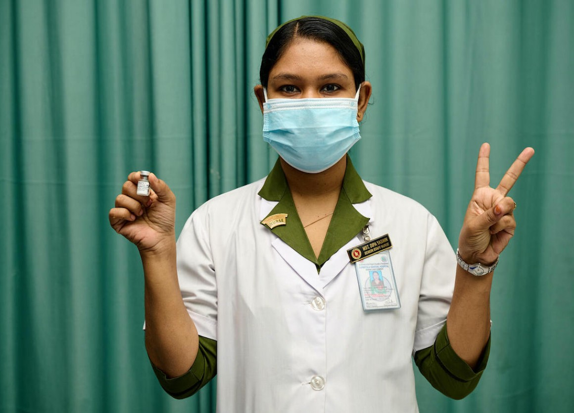 A trained vaccinator at Kurmitola General Hospital, Dhaka, Bangladesh, flashes V for victory — also V for vaccine — as COVID-19 vaccinations ramp up in the country, with support from UNICEF and the COVAX Facility.
