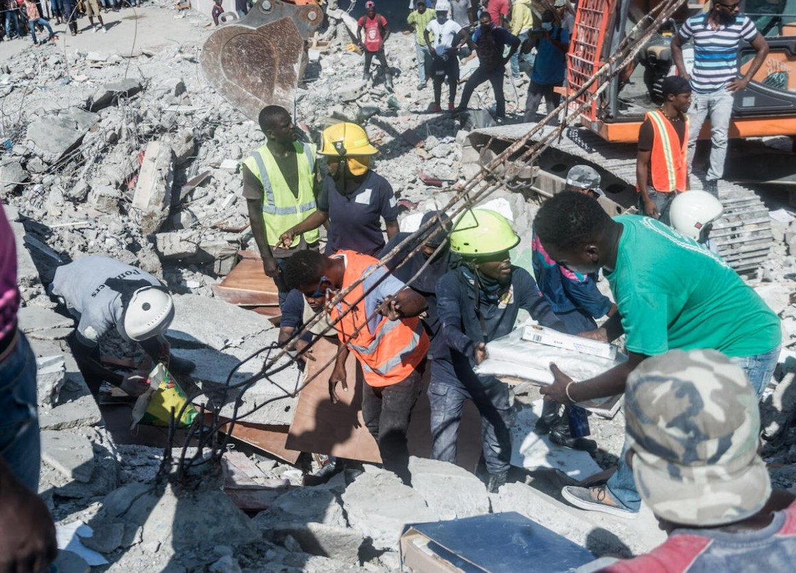 People look for survivors in the rubble in the neighborhood of Dexia 6, Les Cayes, Haiti on August 15, 2021, after a 7.2-magnitude earthquake struck Haiti's southwest peninsula.