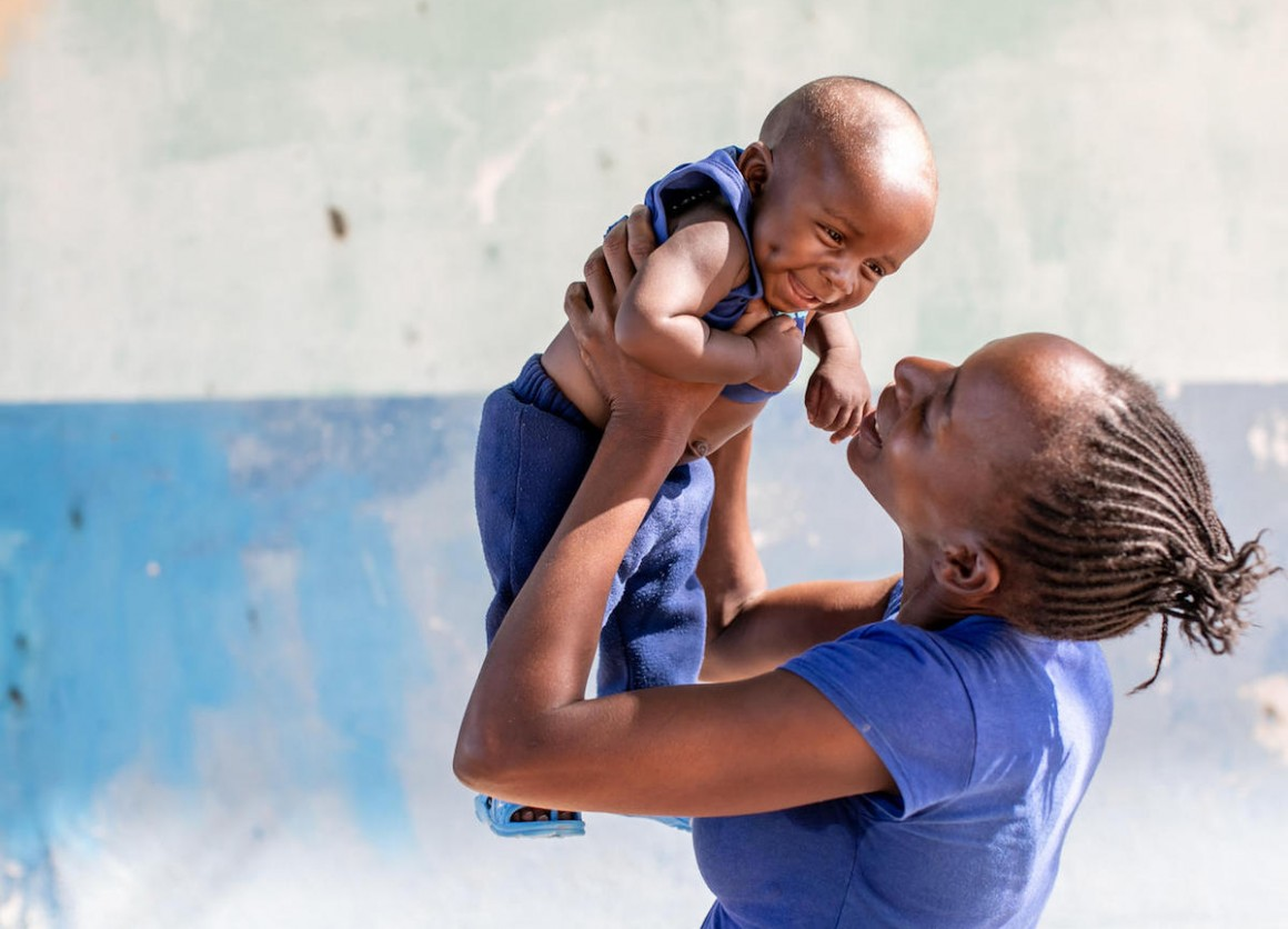 On January 27, 2020, 6-month-old Misheck is held aloft by his mother outside the UNICEF-supported Luumbo Health Center in Zambia.