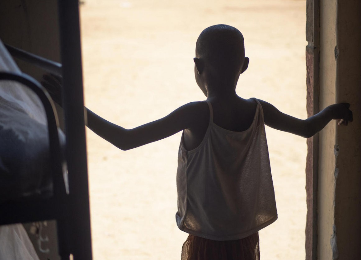 An 8-year-old girl rescued from female genital mutilation stands in a doorway at Kalas Girls Primary School in Uganda's Amudat District.
