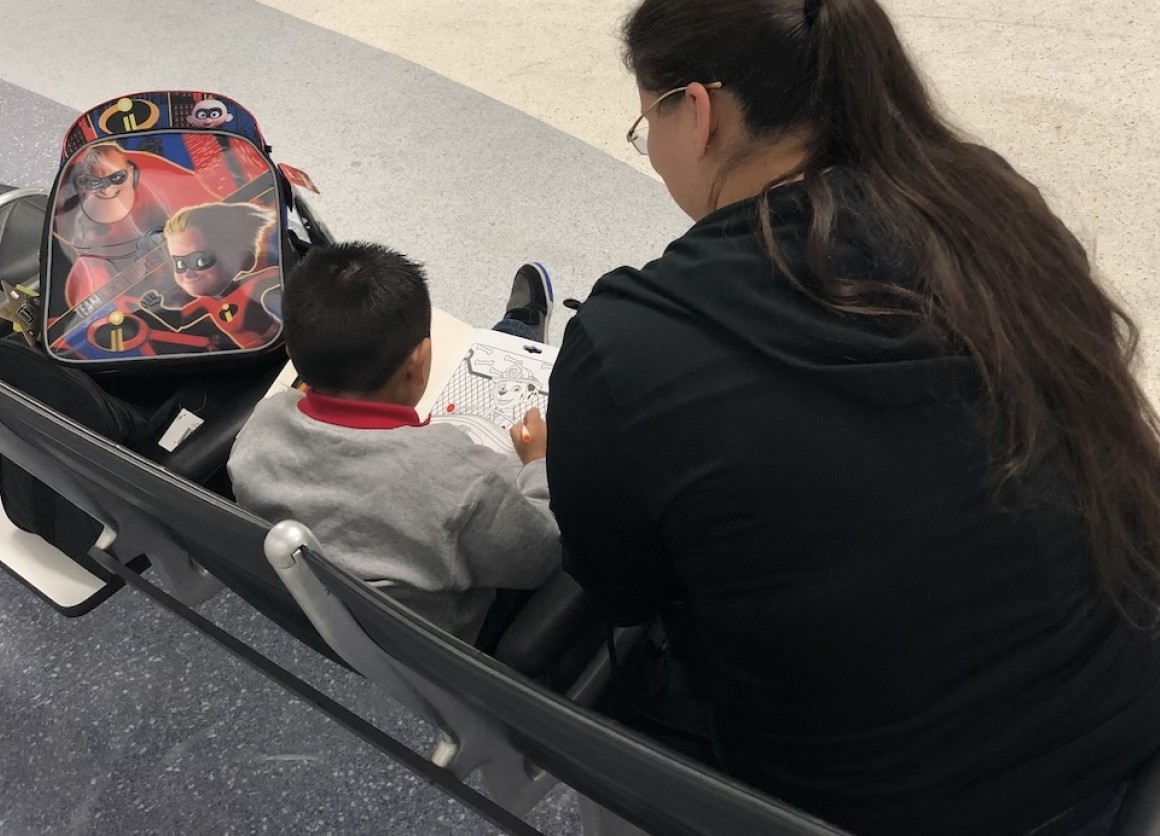 Olivia Pena, deputy program director for the Young Center, sits with a migrant child who got separated from his parents at the U.S. border.