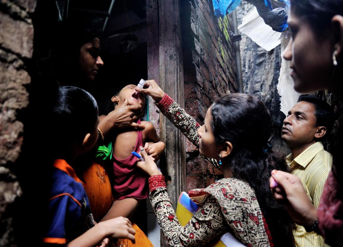 A boy is given a dose of oral polio immunization by a woman.