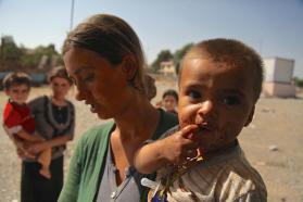 In August 2014, a woman and her young son are among displaced Yazidi children and adults sheltering in Dohuk Governorate, Iraq. UNICEF is providing services for displaced Yazidi  families.