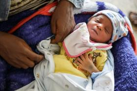 A baby on his mother's lap waits to receive the BCG vaccine in Sierra Leone.