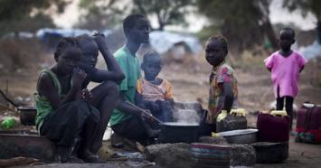 Displaced children gather at a cooking fire in the town of Mingkaman, South Sudan.
