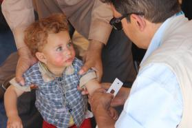 A UNICEF health worker measures the arm of a Yazidi child to check for malnutrition. © UNICEF Syria/2014/Razan Rashidi