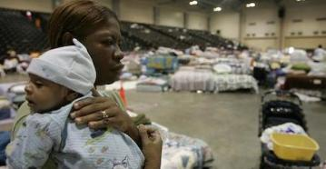 A woman carries her grandson at a shelter for people displaced by Hurricane Katrina.