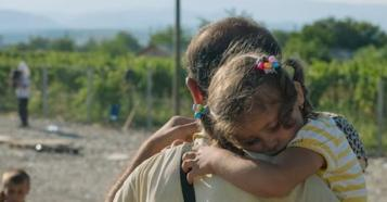Child refugee crisis: A girl rests on her grandfather's shoulder as they wait for temporary transit visas in fYR Macedonia.
