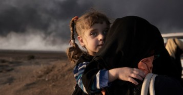 A newly displaced woman carries a child at a check point in Qayyara, south of Mosul on October 31, 2016. UNICEF IRAQ